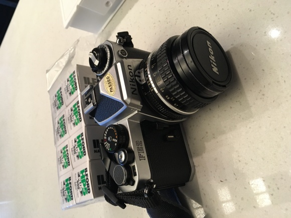 A Nikon FE2 camera on a table with 8 rolls of film behind it.