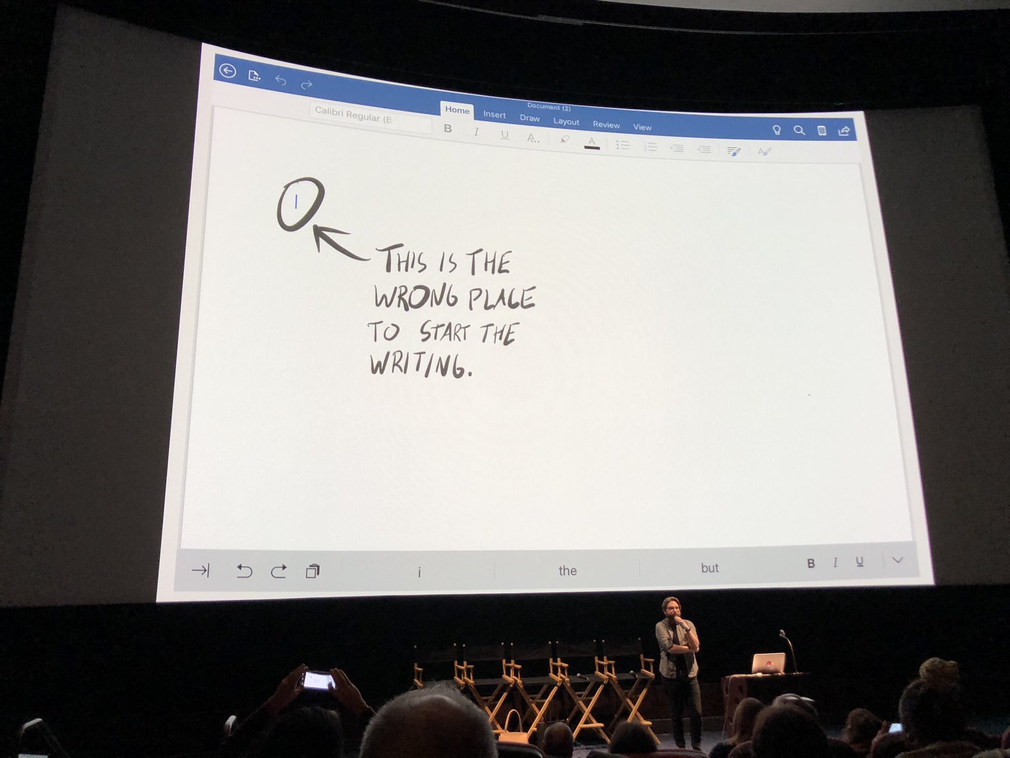 Scott speaking in a movie theatre space in front of a large screen displaying his slides.