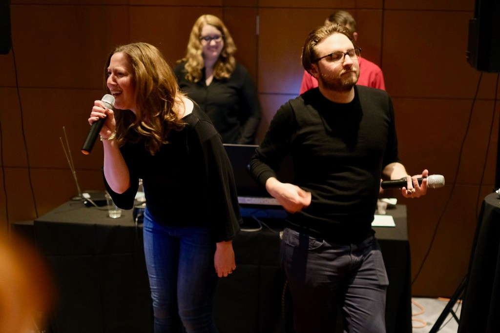 Photograph of the author and his friend Margot singing karaoke. Or rather, Margot is singing and Scott is playing air guitar.